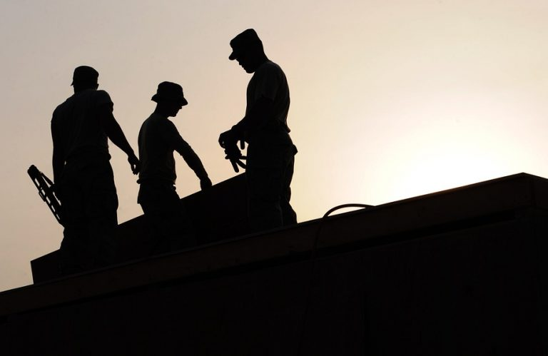 Three construction workers on a roof silhouetted by the setting sun