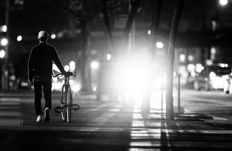 A bike at night silhouetted against headlights, which emphasizes how tricky visibility can be in Oregon and how bicyclists can protect themselves through the use of bike lights and bright or reflective clothing.