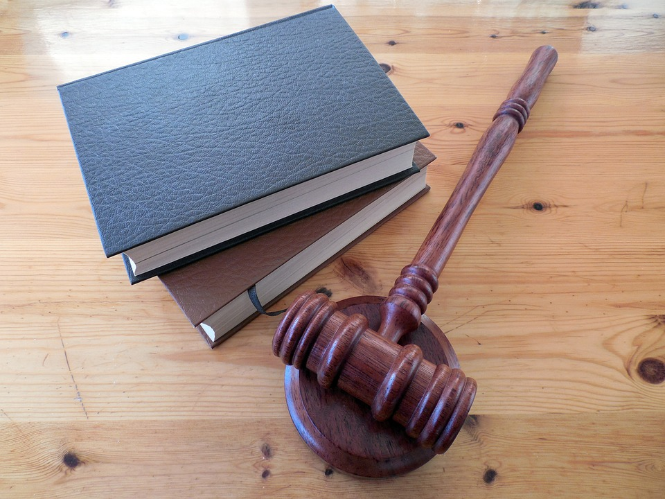 A gavel resting beside two books, pictured to reference the recent rulings in Horton v OHSU and Rains v Stayton Builders Mart, Inc. regarding caps on non-economic damages in the state of Oregon.