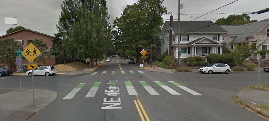 "The NE Tillamook greenway crossing NE 15th Avenue, featuring green ""crossbike"" markings on the asphalt to let drivers know bikers will be crossing the road."