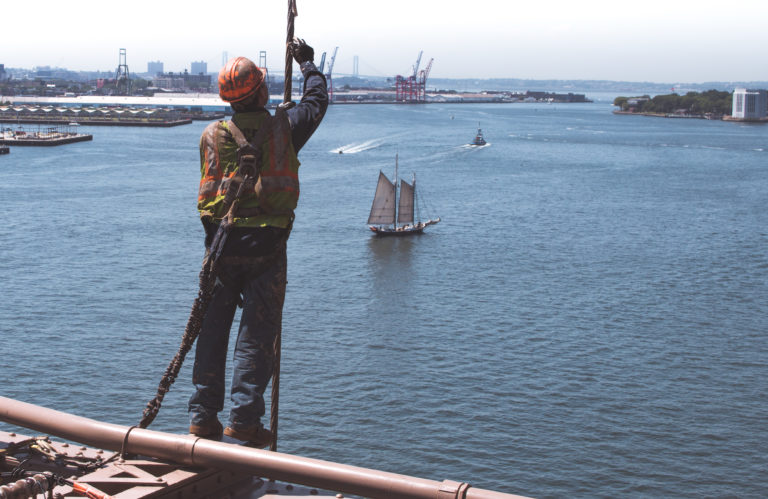 A construction worker on a bridge above water, wearing a hard hat and a safety harness as he works. Adequate construction site safety policies and practices are necessary to protect construction workers.