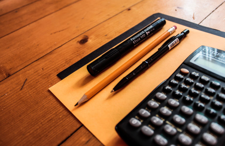 A calculator, pencil, and pens sitting on a desk