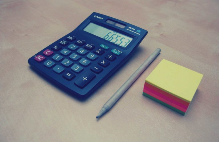 Calculator, pen and stack of post-it notes
