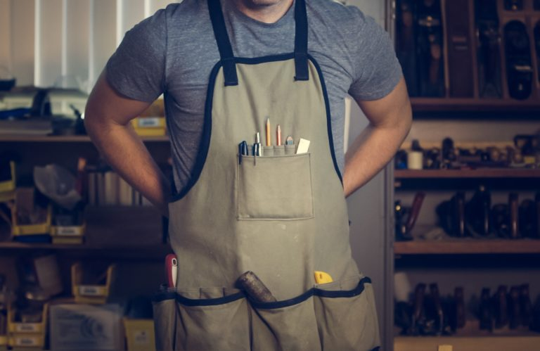 The torso of a white middle-aged male wearing an apron with woodworking tools.