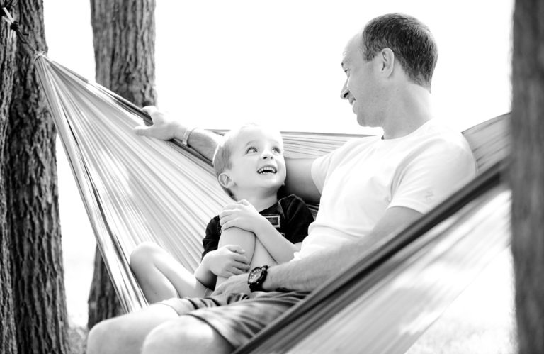 father and son sit in hammock together